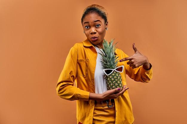 Kobieta w żółtej koszuli wskazuje w dłoni zielonego ananasa w białych okularach przeciwsłonecznych. koncepcja podróży