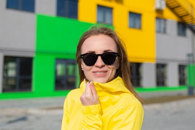 Kobieta w żółtej kurtce i okularach przeciwsłonecznych uśmiechająca się na tle budynków w jasnych kolorach