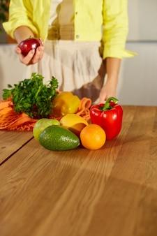 Kobieta w żółtej kurtce rozpakowywanie siatkowej torby na zakupy ze zdrowymi warzywami i owocami w kuchni
