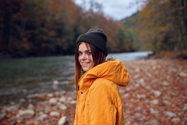 Kobieta w żółtej kurtce w lesie jesienią opadłych liści rzece