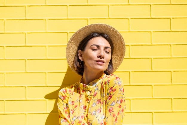 Kobieta w żółtej letniej sukience i kapeluszu na żółtym murem spokojna i pozytywna, cieszy się słonecznymi letnimi dniami