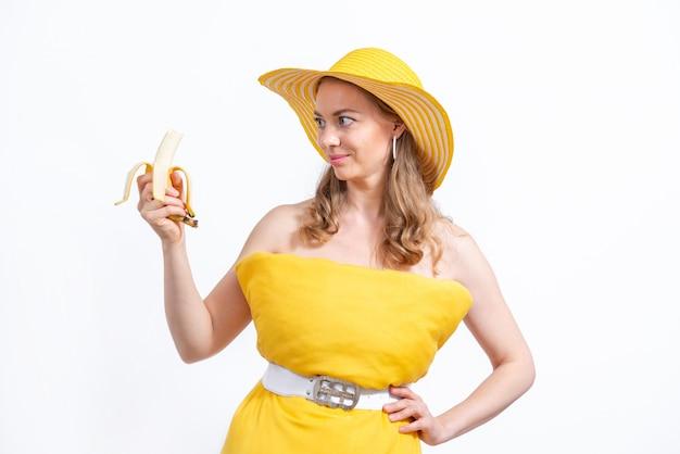 Kobieta w żółtej poduszce sukienka i kapelusz trzyma banana na białym. koncepcja lato z jedzeniem. wyzwanie poduszki z powodu izolacji domu.
