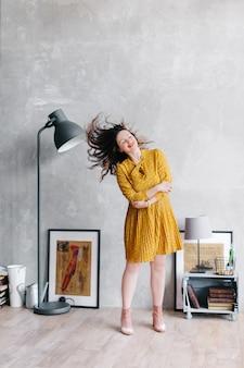 Kobieta w żółtej sukience macha włosami. dziewczyna zostaje w domu i wariuje na punkcie izolacji, jej włosy lecą. modny portret w stylowym wnętrzu.
