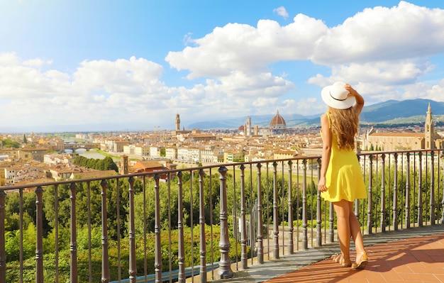 Kobieta w żółtej sukience wygląda na oszałamiającą panoramę florencji we włoszech. pełna długość wesołej, ładnej dziewczyny z toskanii.