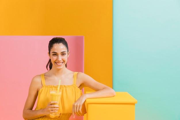 Kobieta w żółtej sukience ze szklanką soku