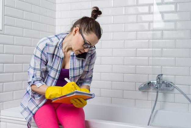 Kobieta w żółtych gumowych rękawiczkach opowiada na telefonu writing w notatniku
