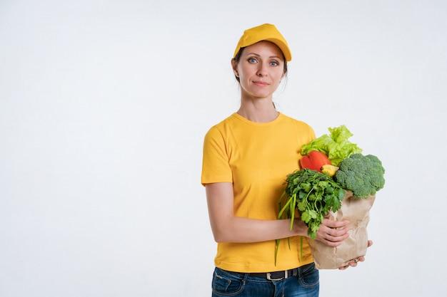 Kobieta w żółtych ubraniach, dostarczająca paczkę jedzenia, na białym tle