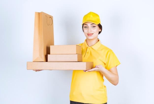 Kobieta w żółtych ubraniach trzymająca paczki ręką w białej ścianie