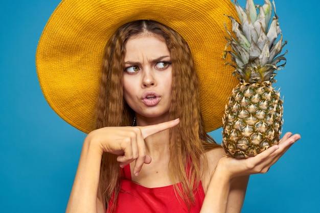 Kobieta w żółtym kapeluszu z ananasem w rękach emocje zabawa styl życia lato owoce niebieski.