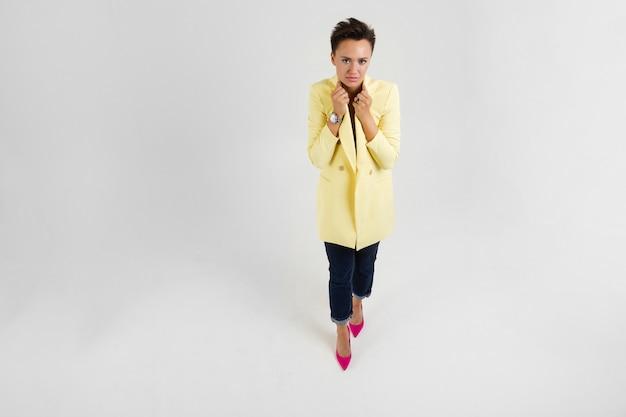 Kobieta w żółtym płaszczu jesiennym jest zimna