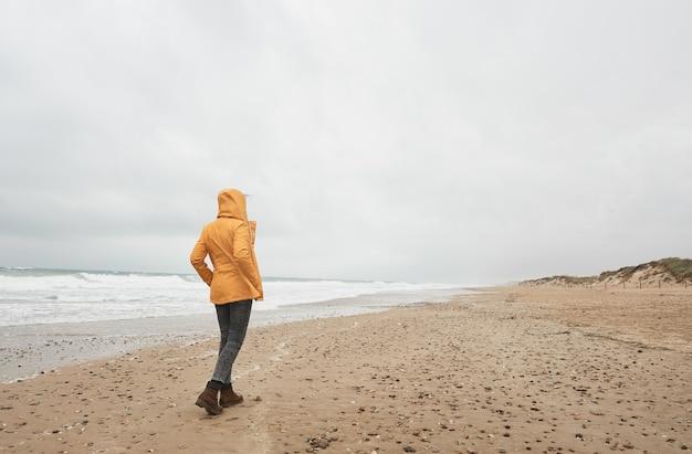 Kobieta w żółtym płaszczu, patrząc na morze. spaceruj po plaży podczas złej pogody.