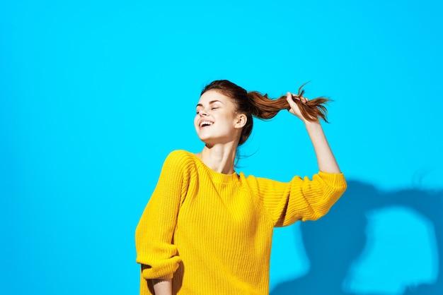 Kobieta w żółtym swetrze pozowanie moda fryzurę niebieskie tło. zdjęcie wysokiej jakości