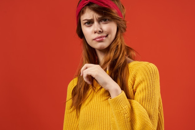 Kobieta w żółtym swetrze z czerwoną opaską moda. zdjęcie wysokiej jakości