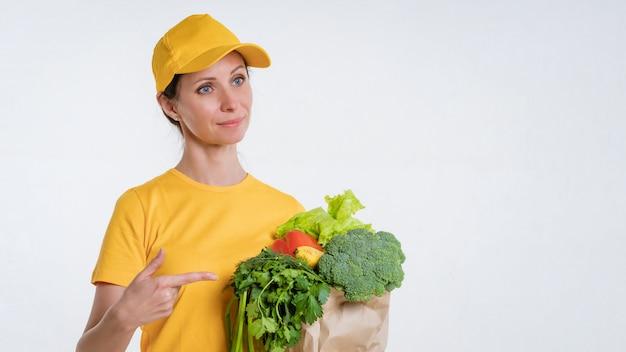 Kobieta w żółtym ubraniu, dostarczająca paczkę jedzenia, na białym