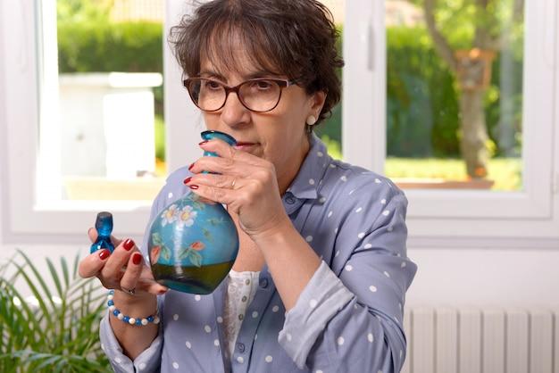 Kobieta wącha butelkę likieru