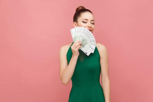Kobieta wącha pieniądze i uśmiecha się