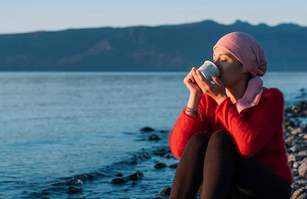 Kobieta walcząca z rakiem popijając herbatę na brzegu jeziora