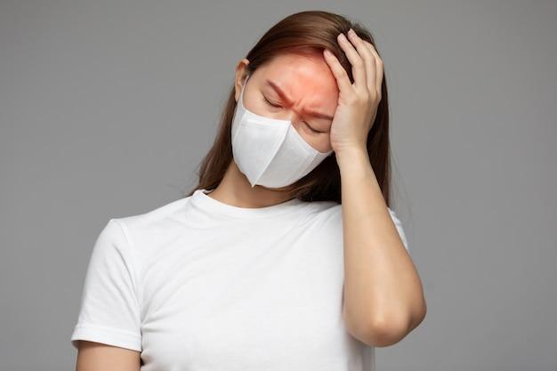 Kobieta waring maska ochronna przed koronawirusem i zanieczyszczeniem powietrza ma gorączkę, a więc ból głowy na białym tle na szarym tle, pojęcie opieki zdrowotnej