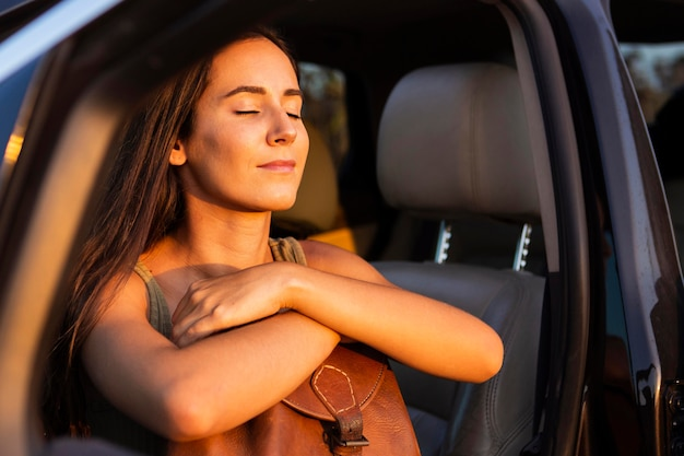 Kobieta wchłaniająca ciepło słońca z fotelika samochodowego