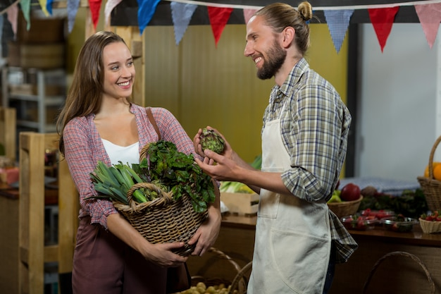 Kobieta wchodząca w interakcje ze sprzedawcą, trzymając kosz zielonych warzyw liściastych