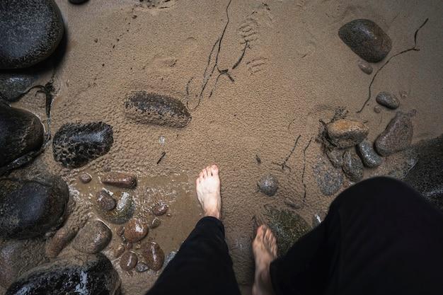 Kobieta wchodzi na piaszczystą plażę w plemont bay na wyspie jersey