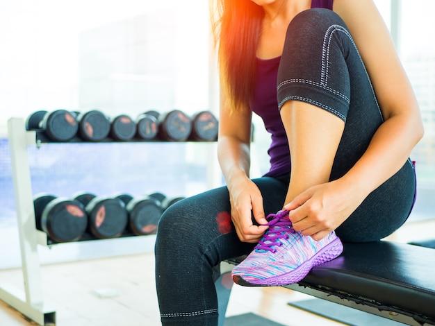 Kobieta wiązana sznurówki do butów. żeński sport sprawności fizycznej biegacz dostaje przygotowywający dla jogging w gym pokoju