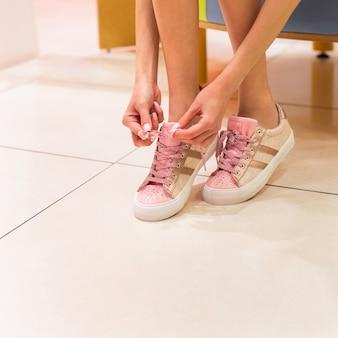 Kobieta wiązanie butów. różowe błyszczące buty dziewczyna kolor na białym tle