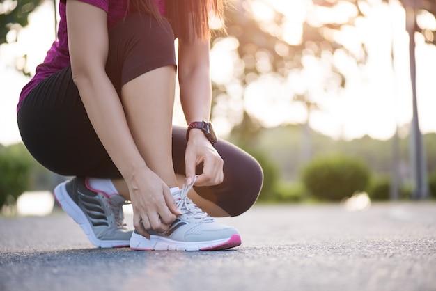 Kobieta wiązanie sznurówki do butów, przygotowuje się do biegania w tle ogród.