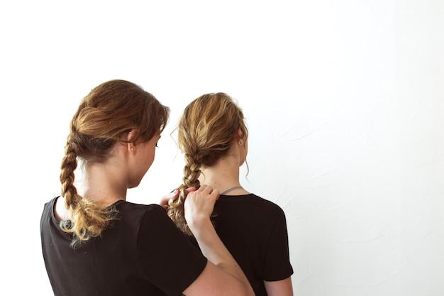 Kobieta wiąże jej siostry warkocz przeciw białemu tłu