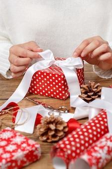 Kobieta wiąże kokardę wstążki na owinięty prezent z bliska
