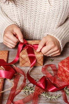 Kobieta wiąże łuk wstążki i zawijanie prezentów z bliska