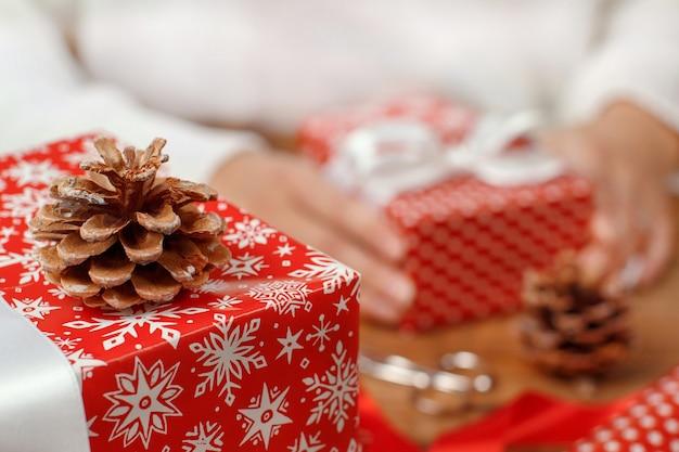 Kobieta wiąże łuk wstążki na zawiniętym prezentu z bliska
