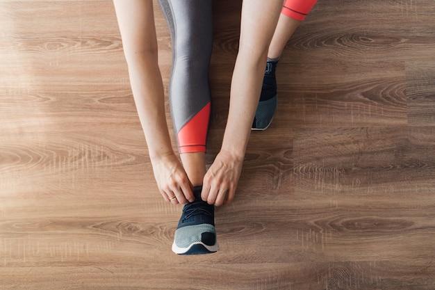 Kobieta wiąże w górę jej sportów butów podczas gdy siedzący na podłoga, odgórny widok