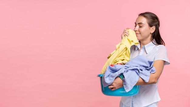 Kobieta widok z boku wącha czyste ubrania