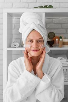 Kobieta widok z przodu przy użyciu kremu do twarzy