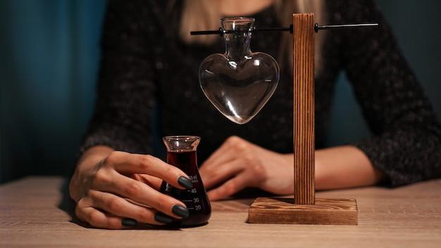 Kobieta wiedźma przygotowuje eliksir. czerwony eliksir miłosny w szklanym słoju w kształcie serca. uwielbiam magiczną koncepcję