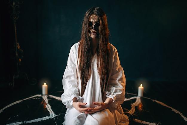 Kobieta wiedźma z głową czaszki siedzi w kręgu pentagram ze świecami. rytuał mrocznej magii, okultyzm