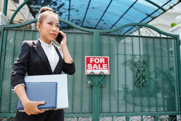 Kobieta wietnamska agentka nieruchomości z dokumentami w rękach, stojąca przy bramie domu na sprzedaż i rozmawiająca przez telefon