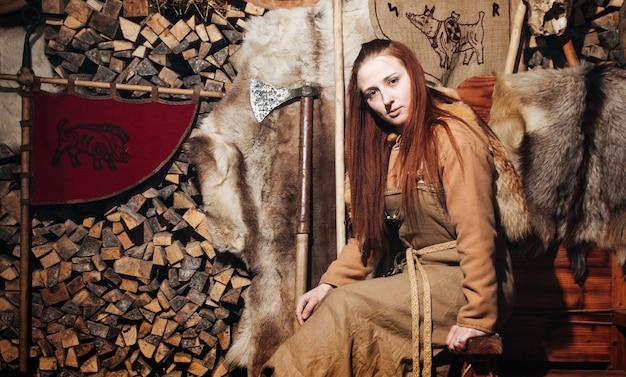 Kobieta wikingów pozuje na tle starożytnego wnętrza wikingów.