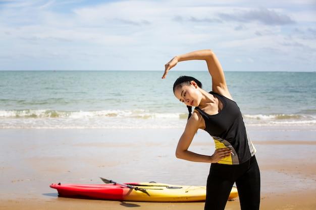 Kobieta wiosłowania kajakiem przez tropikalną plażę. spływy kajakowe po phuket w tajlandii