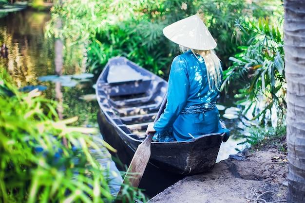 Kobieta wiosłuje drewnianą łodzią