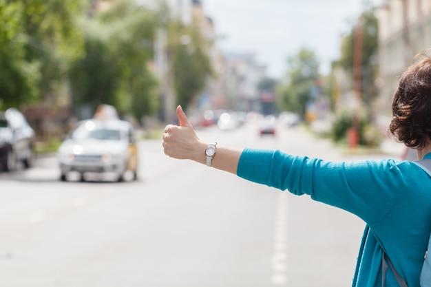 Kobieta wita taksówki chodzenie w ulicy miasta z torebką