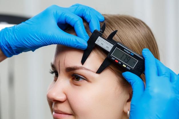 Kobieta wizażystka permanentna rysuje szkic brwi na twarzy swojej klientki.
