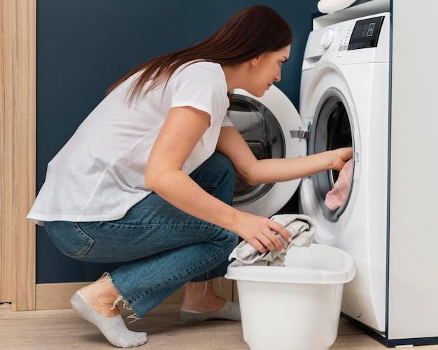 Kobieta wkłada brudne ubrania do pralki