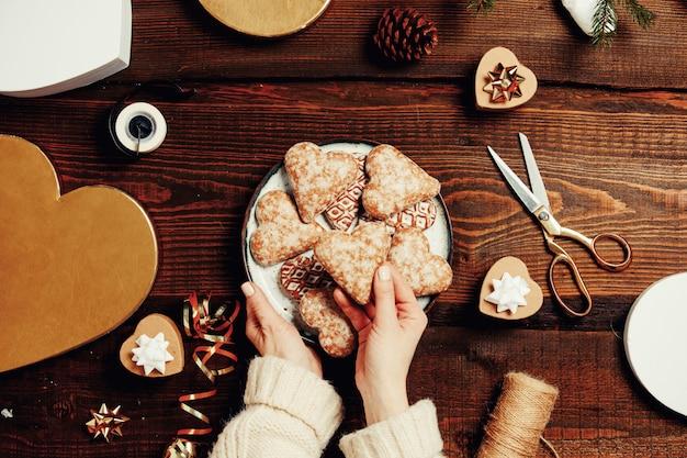 Kobieta wkłada ciasteczka do pudełka z prezentami