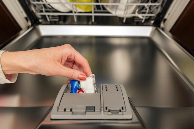 Kobieta wkłada kapsułkę do zmywarki przed myciem