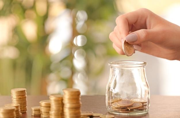 Kobieta wkłada monety do szklanego słoika na stole. koncepcja oszczędności