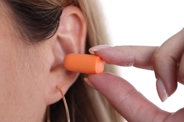 Kobieta wkłada pomarańczowe zatyczki do uszu typy koncepcji zatyczek do uszu do snu