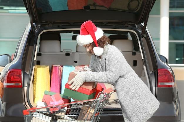 Kobieta wkłada prezenty do bagażnika samochodu na zewnątrz
