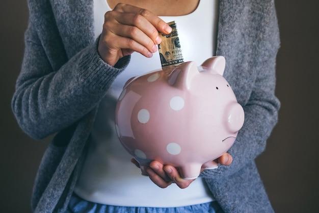 Kobieta wkłada rachunek do smutnej skarbonki kobieta oszczędza pieniądze na płatności domowe rachunki bankowe